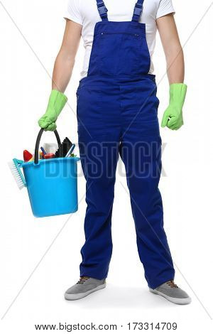 Young man holding bucket with cleaning equipment and supplies on white background