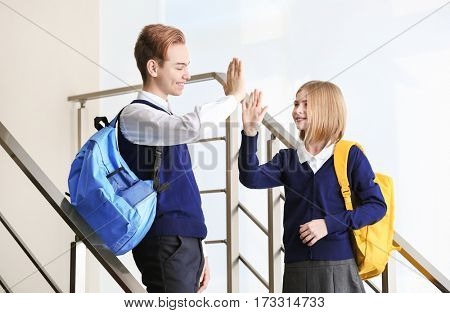 Cute boy and girl in school uniform exchanging high five on stairs