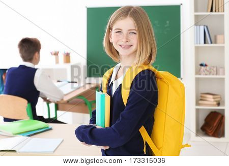 Cute girl with backpack and books standing in classroom