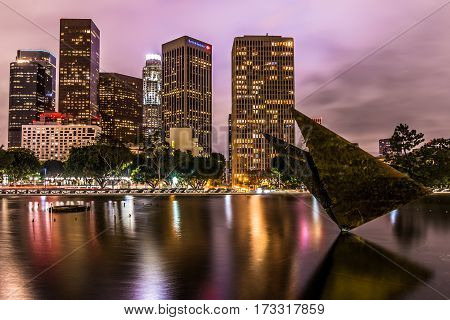 LOS ANGELES, CALIFORNIA - FEBRUARY 19, 2017:  Night view of the reflecting pool at the Los Angeles Department of Power and Water with downtown cityscape and sculpture Colpo d'ala by Arnalda Pomodoro.