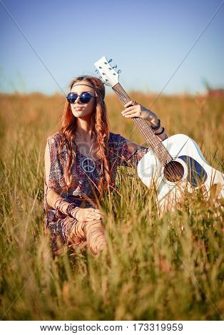 Portrait of a lovely young hippie girl with guitar in the field.