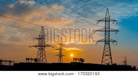 distribution electric substation with power lines and transformers at sunset