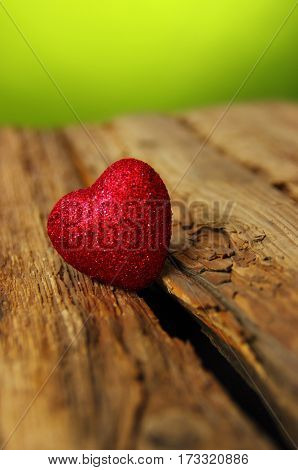 Red heart on a wood and green background