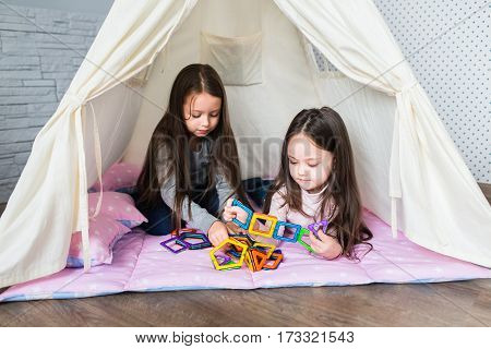 Children playing at home indoors in a teepee tent