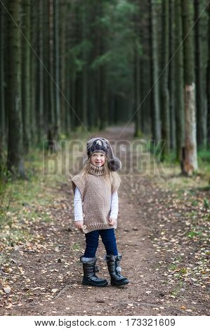 Fashion child in knitted sweater walking in the autumn forest. Late in the fall.