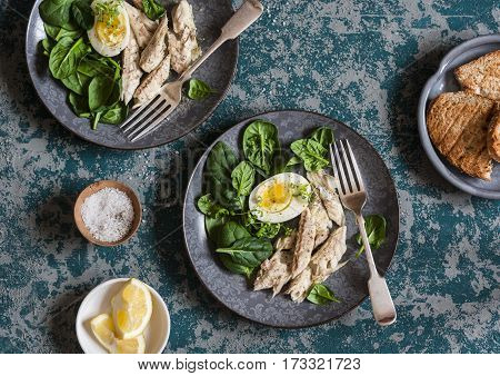 Poached mackerel spinach and egg salad on a dark background top view. Delicious healthy food concept