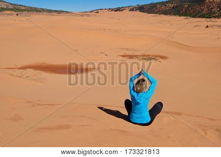 Woman meditating in desert. Coral Pink Sand Dunes State Park. Cedar City. Kanab. Utah. United States.