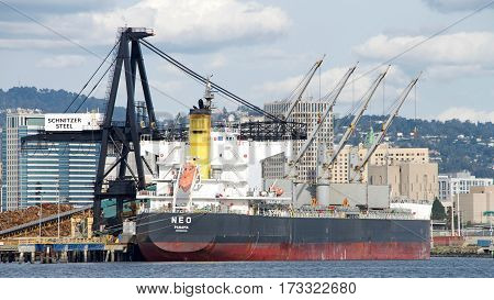 Oakland CA - February 24 2017: Bulk Carrier NEO loading at Schnitzer Steel at the Port of Oakland. Schnitzer Steel recycles scrap metal into finished steel products such as rebar and wire rod.