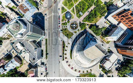 Aerial city view with crossroads, roads, houses, buildings, parks and parking lots. Copter drone helicopter shot. Panoramic wide angle image.