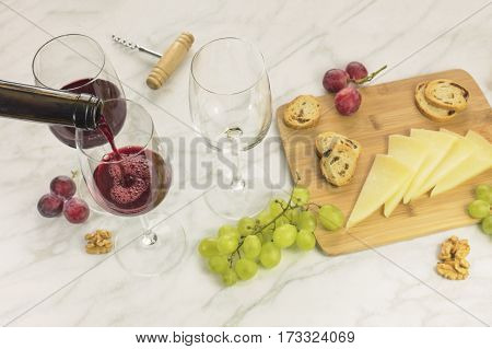 Red wine poured into a glass at a tasting, with cheese, bread, and grapes. Selective focus