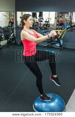 Young woman doing fitness exercises with expander in gym