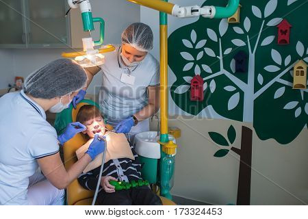 dentist doctor and a nurse curing child teeth