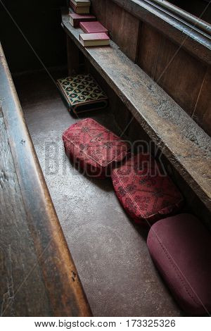 Four colorful kneeling cushions under an old oak church pew, with several hymn books,diagonally photographed.