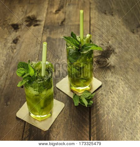 A square photo of mojito cocktails with mint leaves, wedges of lime, and drinking straws, on a dark wooden background with copy space