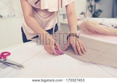 Dressmaker outlining pattern of jacket on cloth