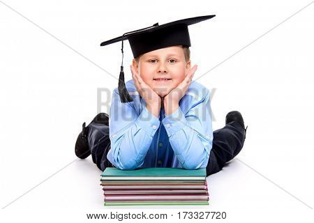 Portrait of a big confident smart boy wearing academic hat. Education. Copy space. Isolated over white background.