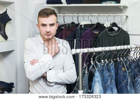 Portrait of young confident man with arms crossed standing in front of clothes rail