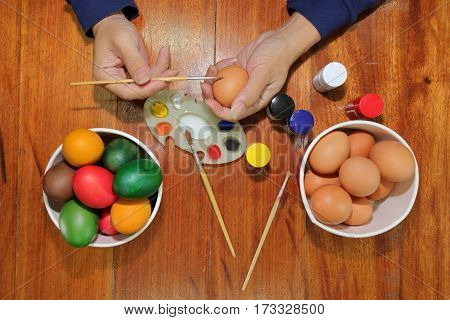 Top view of colorful Easter eggs are being painted with paintbrush and palette by young man on wooden table.