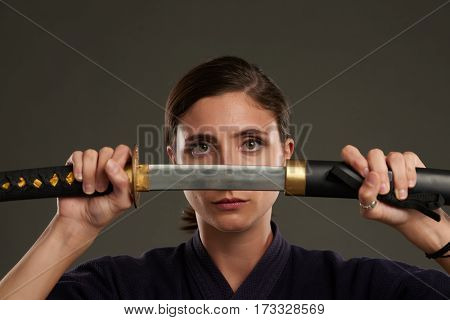 Unsmiling young woman unsheathing her katana sword