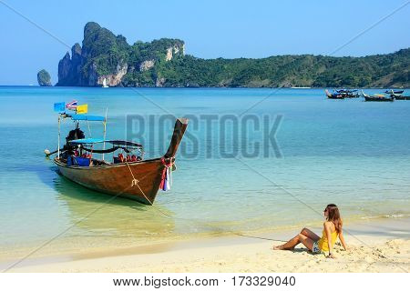 Young woman sitting at Ao Loh Dalum beach on Phi Phi Don Island Krabi Province Thailand. Koh Phi Phi Don is part of a marine national park.
