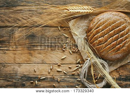 Cereal flatbread ears of wheat and rye grain on an old wooden table rustic style