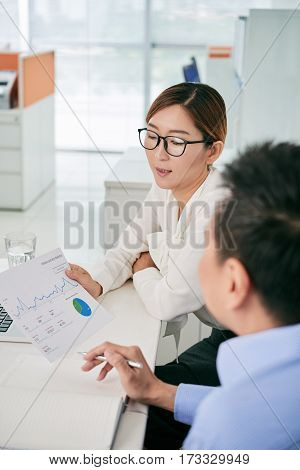 Female financial manager showing diagram to coworker