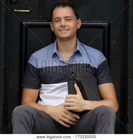 Happy Male Student With Satchel Sitting by Door