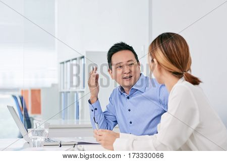 Cheerful Asian businessman talking to female coworker in office