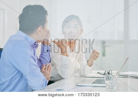 Pretty business lady talking to male colleague in meeting room