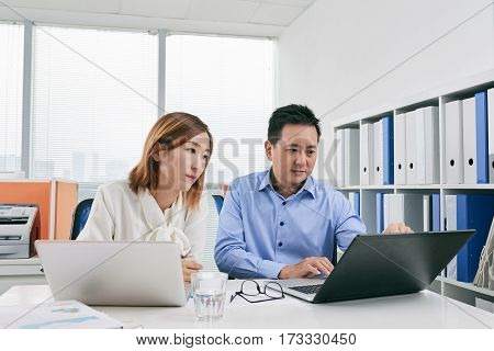 Asian business people using laptops at meeting in office