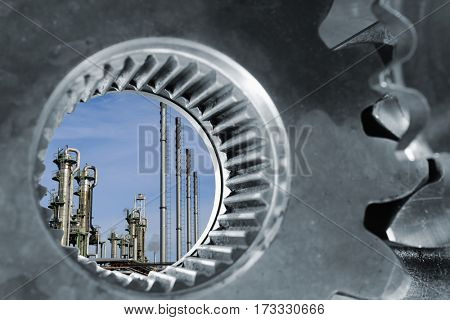 oil and gas refinery seen through a large gears and cogwheel