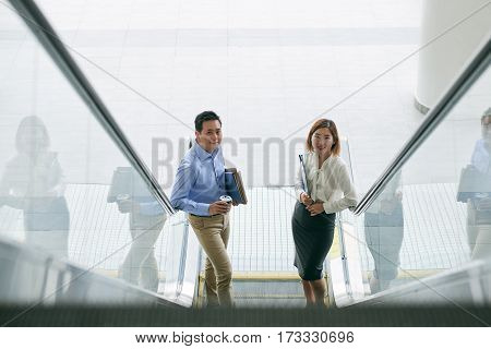 Cheerful business people standing on escalator, view from above