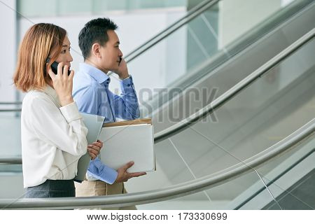 Side view of business people calling on the phone when going to work
