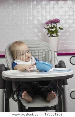 Funny baby playing with plate and spoon on baby chair.
