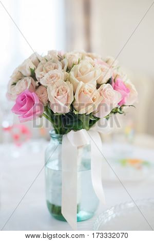 Beautiful wedding bouquet of delicate beige roses stands on the table