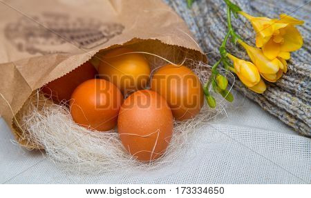 Easter colored eggs in a paper bag with the flower of freesia, spring mood