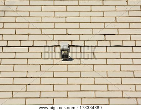 Motion Sensor on the house white brick wall facade. Motion Flood Light. How to Choose and Install Motion Detector Lighting.