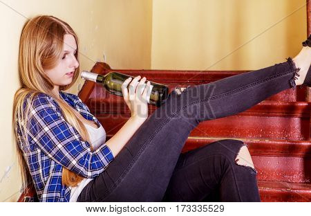 Drunk young woman with bottle of alcohol