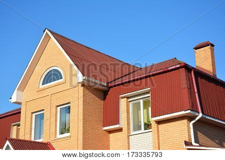 Attic roof exterior with asphalt shingles and plastic rain gutter system. Mansard house roofing type.