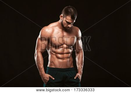 Strong Athletic Man - Fitness Model showing his perfect back isolated on black background with copyspace.
