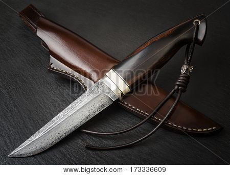 handmade knife Damascus of mosaic with a mammoth tusk on a black background