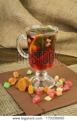 Toning ginger tea with lemon and mint. Glass cup of tea with ginger and lemon and candied fruit on a wooden background, space for text