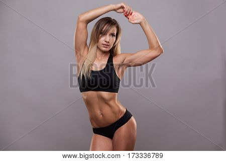 Beautiful athletic woman in sporty cloths is raising her hands up and showing her perfect body, isolated on grey background with copyspace.