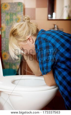 Sick young woman leaning on open toilet seat an vomiting.