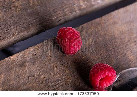 Fresh juicy raspberry on wooden plank