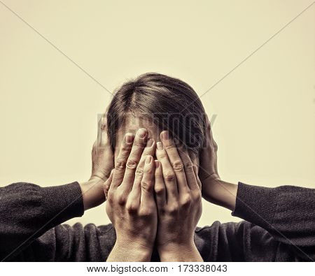 Concept of fear domestic violence. Woman's hands covers her face and ears.
