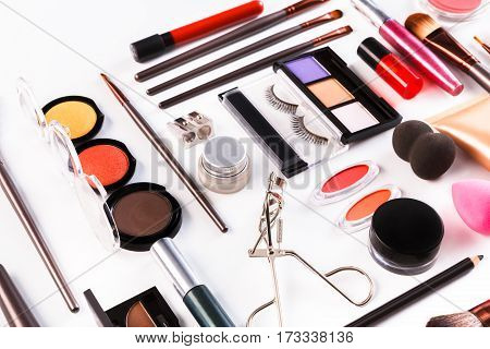 Makeup cosmetics, brushes and other essentials on white background. Flat lay. Multicolored beauty tools and products collection, lipsticks, eyeshadow, mascara, sponge, eyelash curler