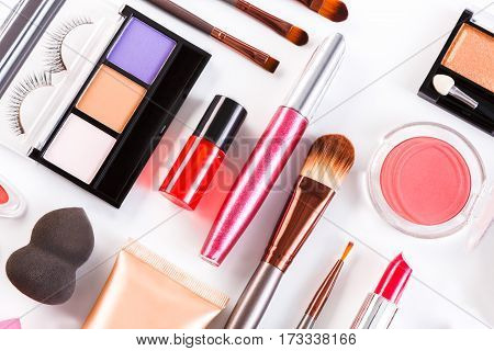 Makeup cosmetics, brushes and other essentials on white background. Top view, flat lay. Multicolored beauty tools and products collection, lipsticks, eyeshadow, blush, sponge, eyelashes and more