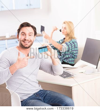 Toned of happy young man smiling for camera and showing credit card. Bearded man sitting at table with computer on while his girl friend powdering her face on background.