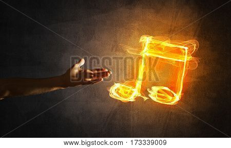 Close up of person hand and fire music symbol on dark background